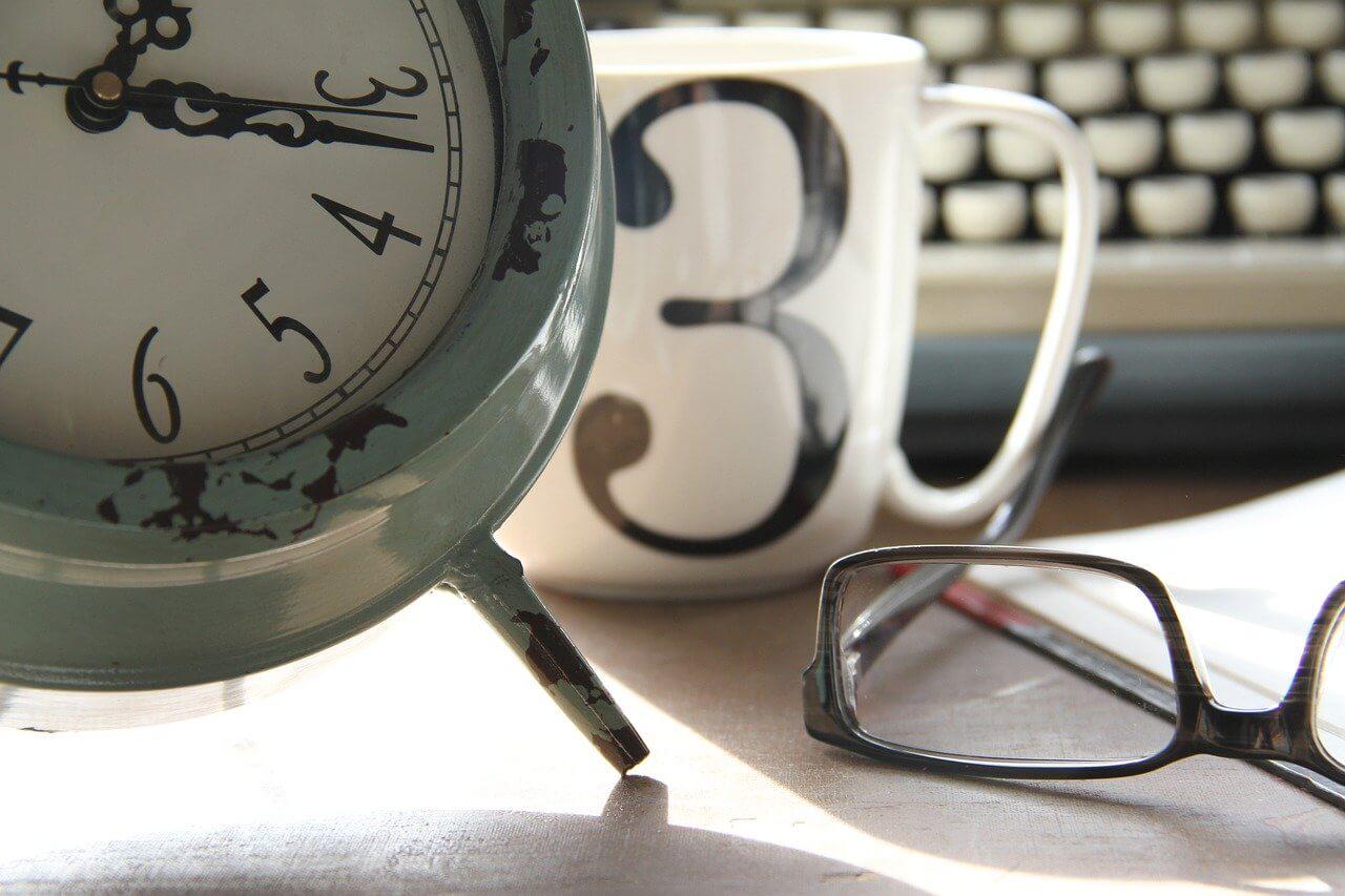 Ein altmodischer Wecker, eine Tasse mit der Zahl 3 sowie eine Brille auf einem Tisch, eine Schreibmaschine im Hintergrund-eine Arbeitsumgebung