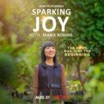 Sparking Joy with Marie Kondo. Marie Kondo ist vor Bäumen und Sträuchern abgebildet. Sie lächelt.